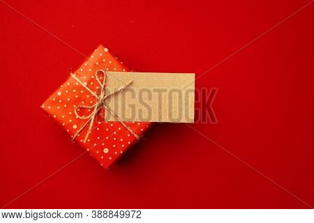 Blank Sheet Of Paper And Wrapped Present For Christmas Celebration On Red Background