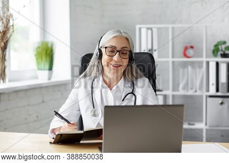 Portrait Of Senior Grey-haired Female Doctor In Her Office Using Laptop For Video Chat With A Patien