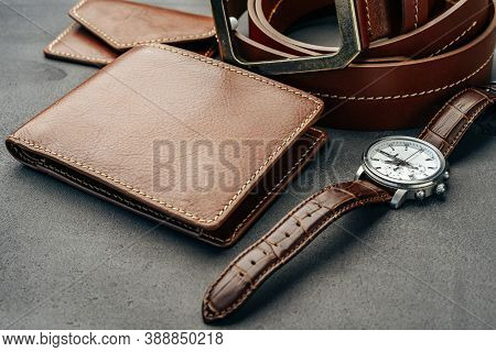 Male Watch And Leather Wallet On Dark Grey Surface