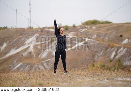 Young Woman Doing Warm-up In Hilly Terrain. Adult Female In Black Casual Clothes Doing Sports In Fre