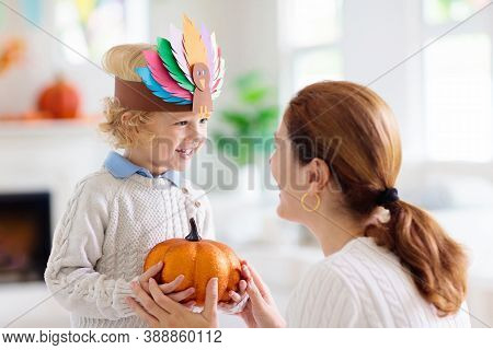 Child And Mother Celebrate Thanksgiving. Kid Holding Pumpkin In Paper Turkey Hat.