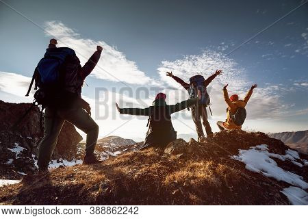 Four Happy Hikers Stands In Winner Poses At Mountain Top At Sunset Time