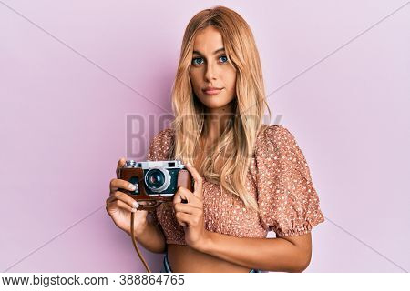 Beautiful blonde young woman holding vintage camera relaxed with serious expression on face. simple and natural looking at the camera.