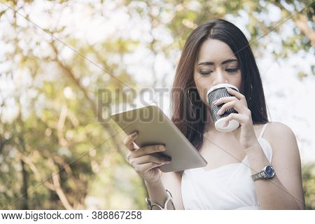Woman Reading Online Article & Explore Online Feminist Website From Tablet  And Drinking Coffee. Sea