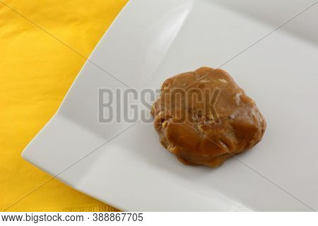 Creole Praline Caramel And Pecan Cluster On White Snack Plate With Yellow Napkin