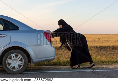 An Islamic Woman Is Pushing A Car Along The Road. Woman Driver - Car Breakdown.