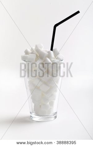White sugar cubes in a glass with tubule isolated on a white