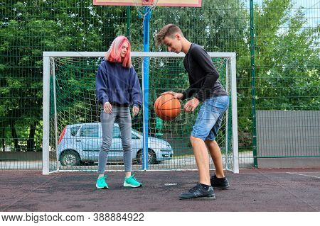 Teenagers Boy And Girl Playing Street Basketball Together, Youth With Trendy Hairstyles Playing Outd