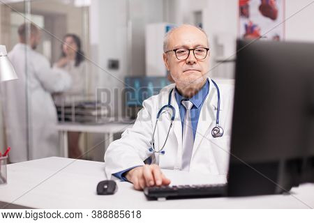 Senior Doctor Typing Expertise Rapport On Computer In Clinic Office While Young Therapist In White C