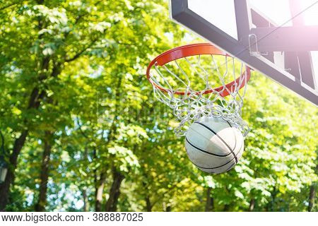 Good Basketball Throw. Basketball Ball Flies Into A Basketball Hoop. Outdoor Basketball Court.