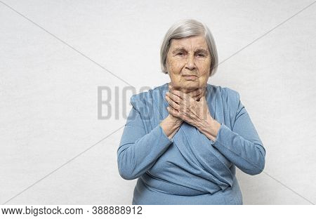Elderly Woman With A Sore Throat. She Holds Her Throat With Two Hands. Copy Space.