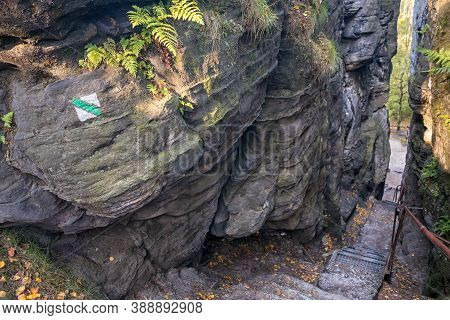 Green Hiking Trail Sign On Rock At The Stairs Through A Rift In The Rocks In Sandstone Mountains, Ti