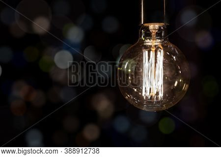 Glowing Vintage Old One Tungsten Lightbulb Hanged On Ceiling Against Black Wall Bokeh Background. Re