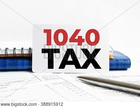 Business Card With Text 1040 Tax Lying On Blue Notebook