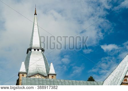 Spire Of The Lutheran Church Against The Cloudy Sky