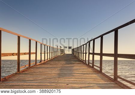 Close-up Of A Wooden Jetty Going Out To Sea Against A Background Of Sunset Color. Closed Exit And Se