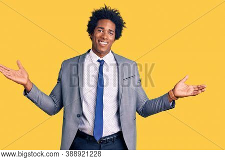 Handsome african american man with afro hair wearing business jacket smiling showing both hands open palms, presenting and advertising comparison and balance