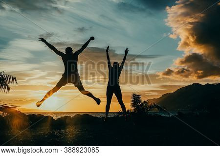 Happy People Jumping Over Sunset, Concept Having Fun And Joy. Two Silhouettes And A Beautiful Sunset