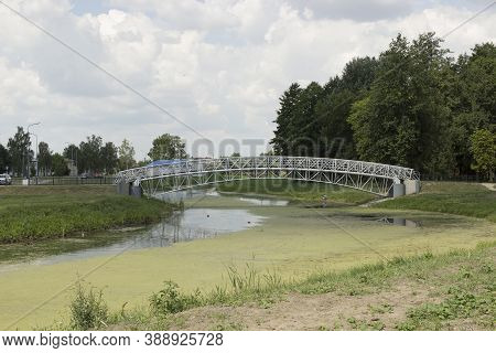 A Modern Metal Bridge Over A Green City River With Blooming Algae. Unkempt River In The Center Of Th