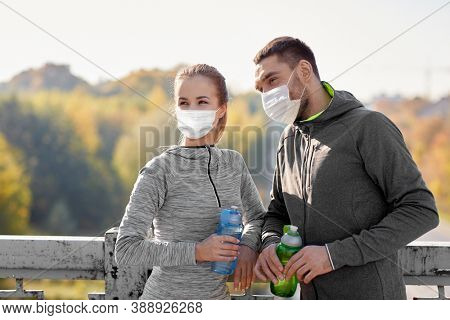 fitness, sport and health concept - smiling couple wearing face protective medical masks for protection from virus disease with bottles of water outdoors