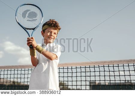 Low Angle Of Smiling Active Preteen Boy In Sportswear Holding Tennis Racket While Practicing Sport G