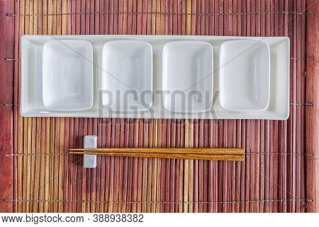 A Japanese-style Table Setting, White Small Cups And Brown Wooden Chopsticks Placed On A Bamboo Plac