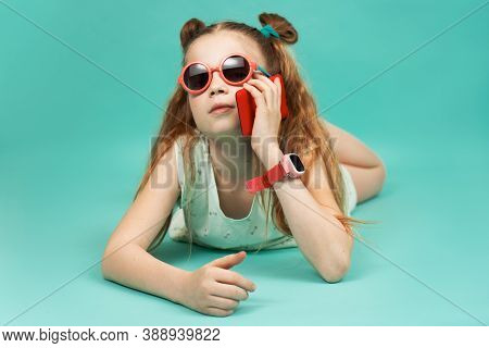 Bright Colors: A Girl In Sunglasses Lies On Her Stomach And Talks On A Smartphone.