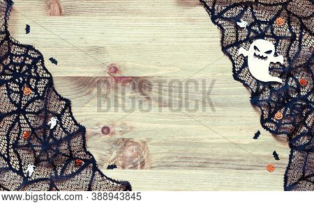 Halloween festive background. Halloween card. Spider web, cobweb lace and spooky ghosts decorations as the symbols of Halloween on the dark wooden background