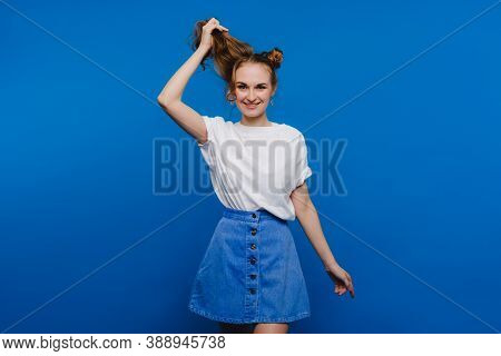 A Young Stylish Girl Pulls Her Hair On A Blue Background, A Model Pulls Her Long Hair.