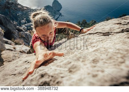 Brave Young Woman Climber Fearlessly Climbs Up Sheer Stone Wall In Mountains, Overcoming Obstacles.