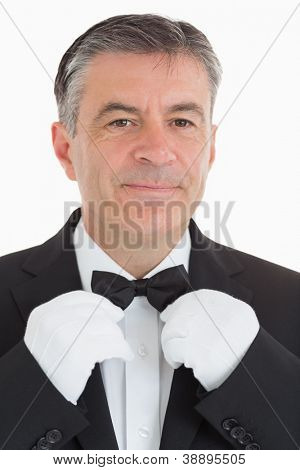 Cheerful and Well-dressed waiter is adjusting his bow tie