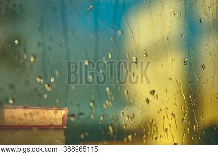 Blurry Wet Background. Rain Background. Old Books On The Windowsill Are Visible Through Wet Glass. C