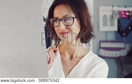 Front View Of Female Dressmaker Looking At Sketch Paper Of New Attire With Contented Facial Expressi