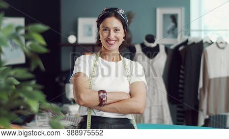 Front View Of Grinning Female Dressmaker With Arms Crossed Standing In Sewing Workshop Looking At Ca