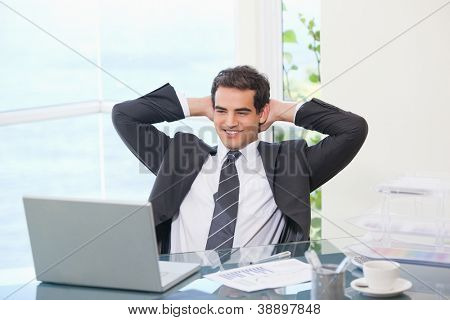 Man crossing his arms behind his head  in an office
