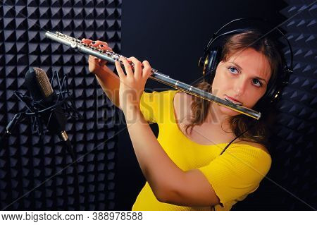 Woman Flutist Plays Boehm Flute, Black Background. Female Flute Player Playing In Music Studio. Reco