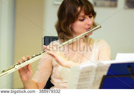 Woman Plays A Large Silver Transverse Flute. A Woman In White Dresses Blows A Orchestral Flute At A