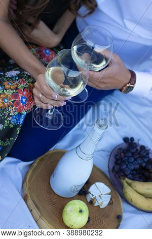 Two Hands Holding Champagne Glasses Near Wooden Stand With Bottle, Grapes And Camembert Cheese On Wh