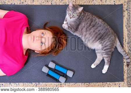 A Tired Woman And A Cat Lie On A Training Mat After A Sports Workout. Concept Of Isolation During Th
