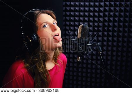 A Young Woman Shows Her Tongue At The Recording Studio. The Singer In The Headphones Was Tired Of Wr