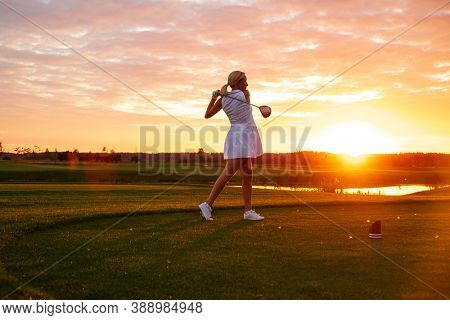 Professional Player Woman Play Golf With Sunset Background .