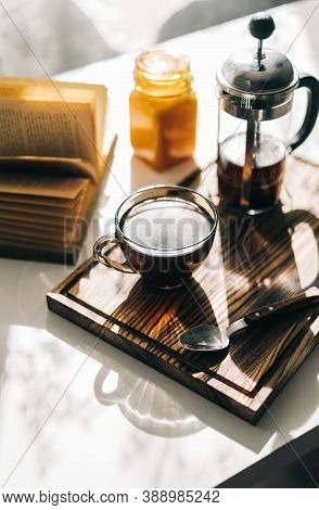 Coffee Brewed In A French Press And A Cup On A Wooden Board With Open Book On A Table. Morning At Ho