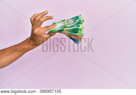 Hispanic hand holding south africa rands banknotes over isolated pink background.