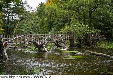 Wooden Pedestrian Bridge Over The River In The Warnow And Milderitz Breakthrough Valley, Hiking Trai