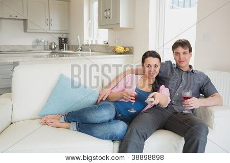 Couple sitting on the couch and drinking while watching television in the living room