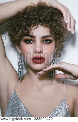 Young beautiful woman with curly hair and smoky eye makeup