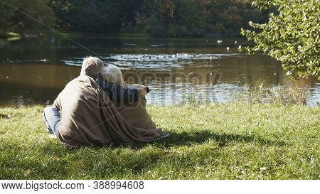 Elderly Gray Haired Couple Siting Near The River Covering With Blanket On Autumn Day. Romance And Ol