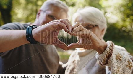Lovely Older Retired Couple Making Heart With Their Hands And Looking At Each Other. Selective Focus