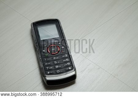 Old Cellular Device Placed On The Table Top In The Home Office, Showing The Screen, Keyboard And Old