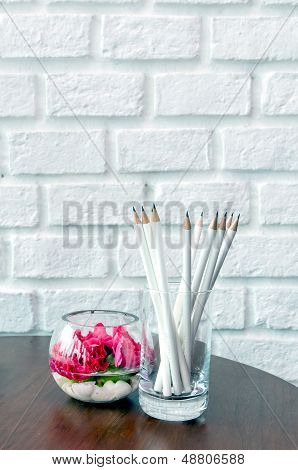 White Pencils In A Glass Beside Beautiful Flower Glass Jar On The Wooden Table And White Brick Wall